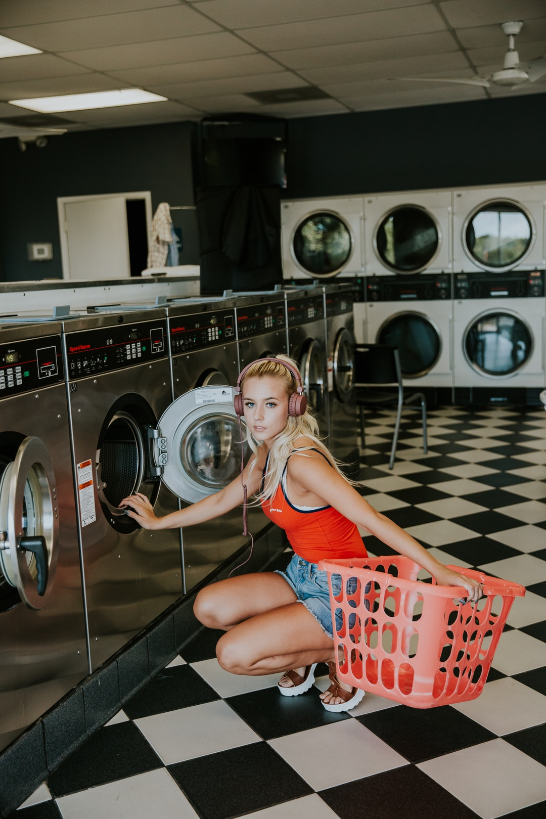 A blonde woman in headphones crouching next to a laundromat with a laundry basket