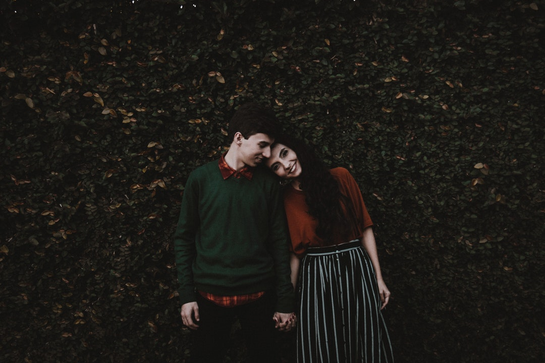 Couple holds hands and leans their heads together in front of a leafy wall in Cianorte