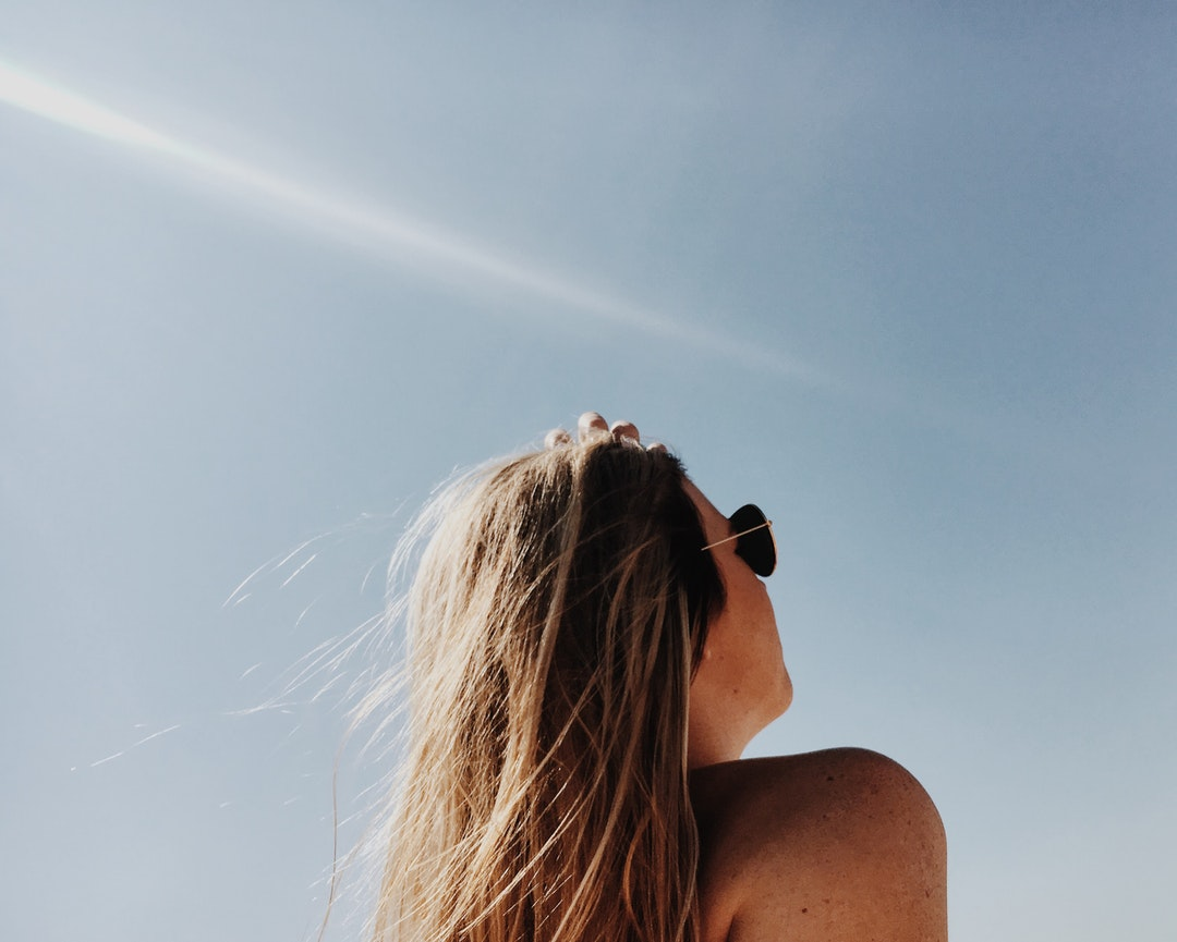A woman in sunglasses looking at the sky
