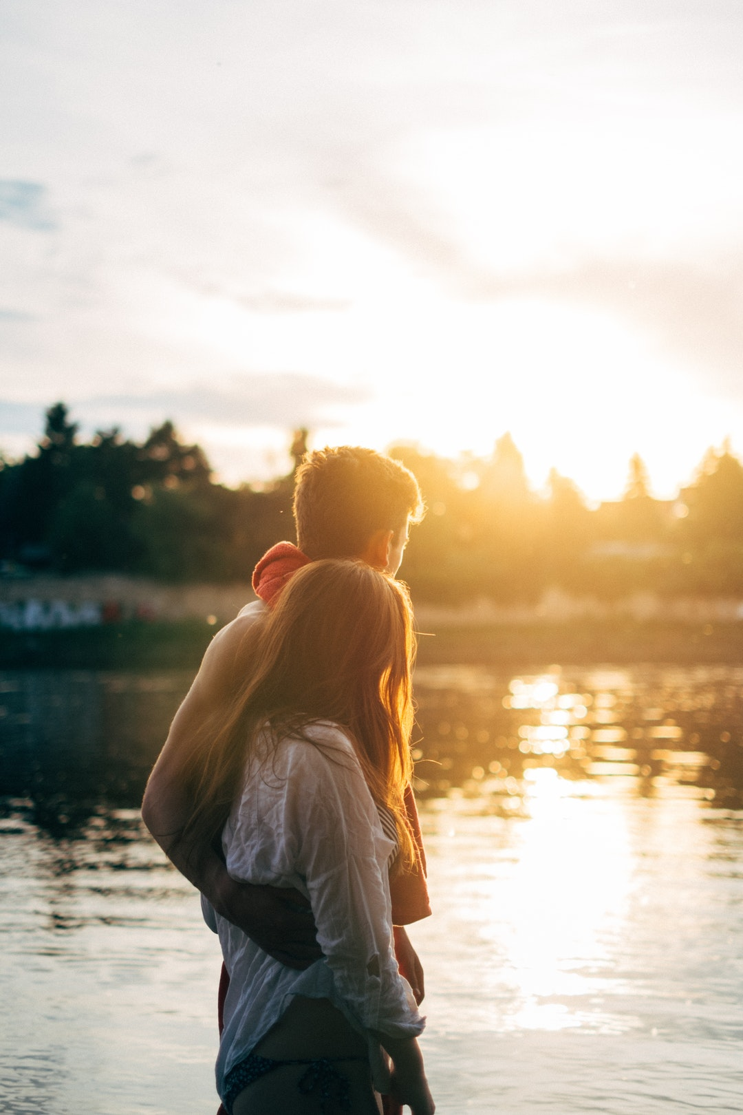 A couple stands by a lake in the sunshine in Dresden. His arm is around her.