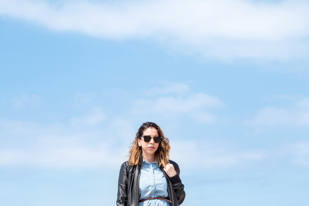 Woman in black leather jacket and sunglasses posing in front of blue skies at Santa Monica State Beach