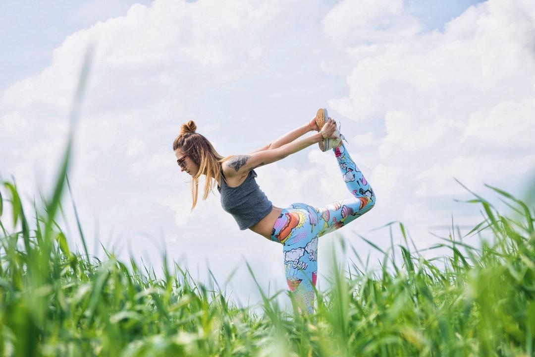 A woman wearing funky leggings doing yoga on the grass in Karczewski