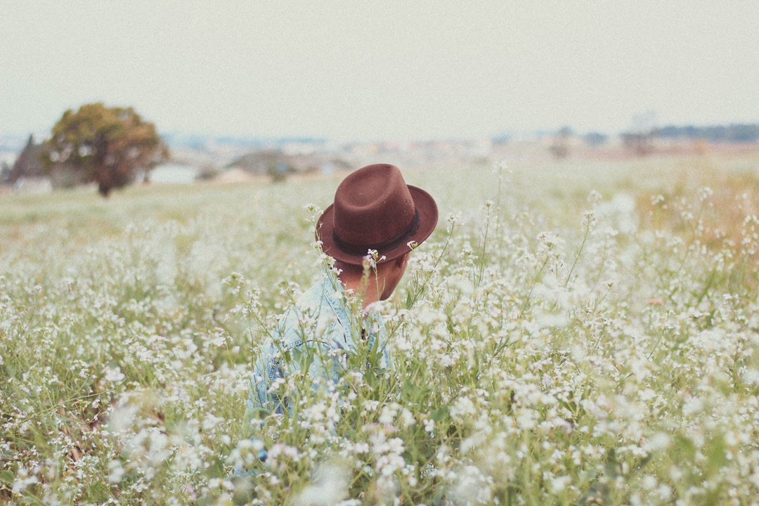 Person in a brown hat sitting in a field of wildflowers