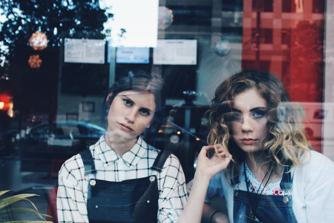 Two young women stare angrily out a reflective window