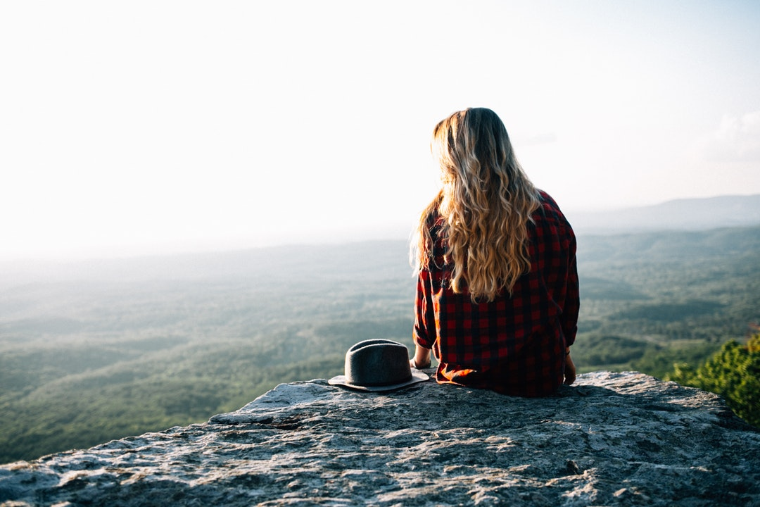 A blonde woman with a hat on her side sitting on a rocky ledge overlooking green plains