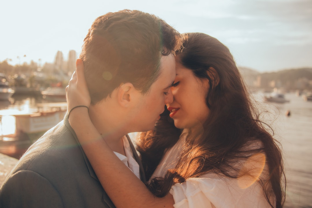 A woman pulls a man into a passionate kiss on sunny Avenida Portugal
