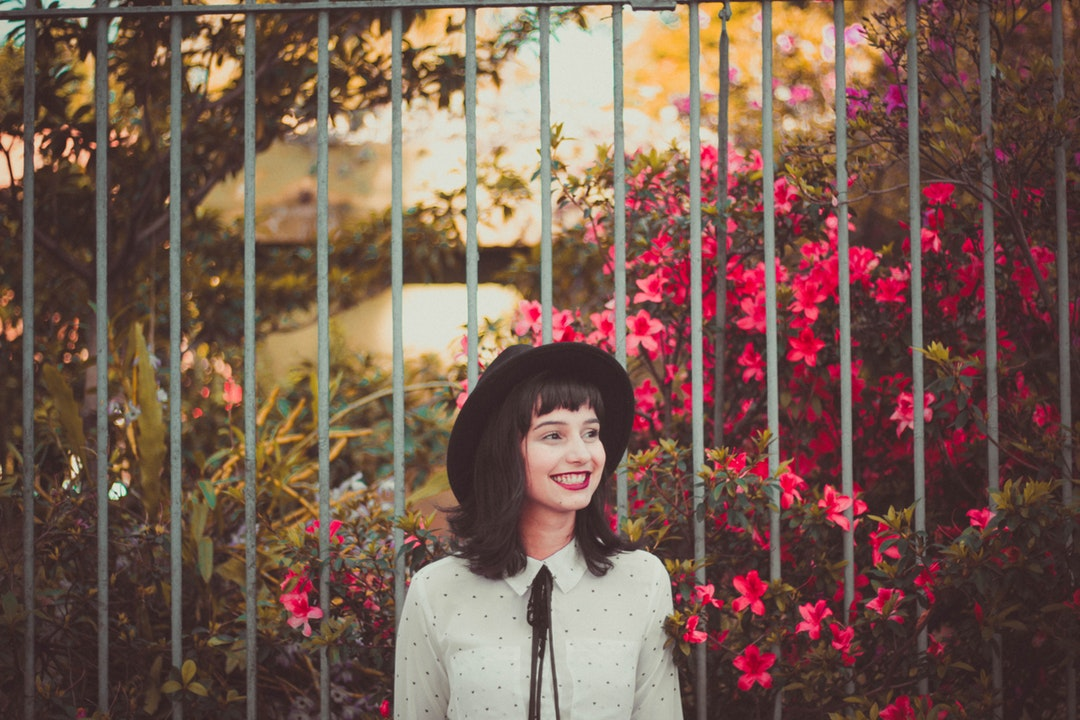 A young woman in a hat smiling while standing next to flower bushes