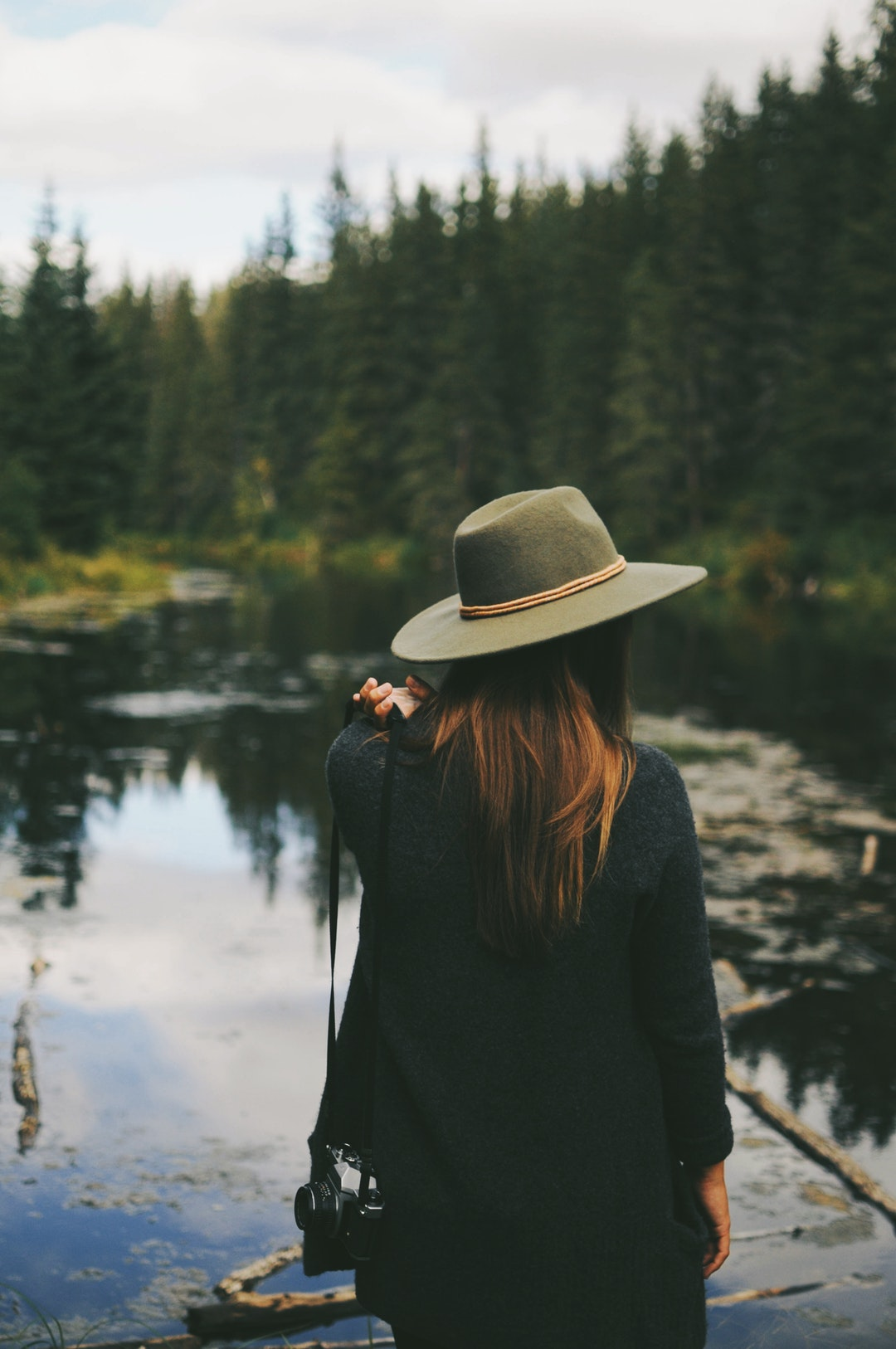 A woman wearing a hat, staring out at the lake at Mactaggart Sanctuary near Edmonton