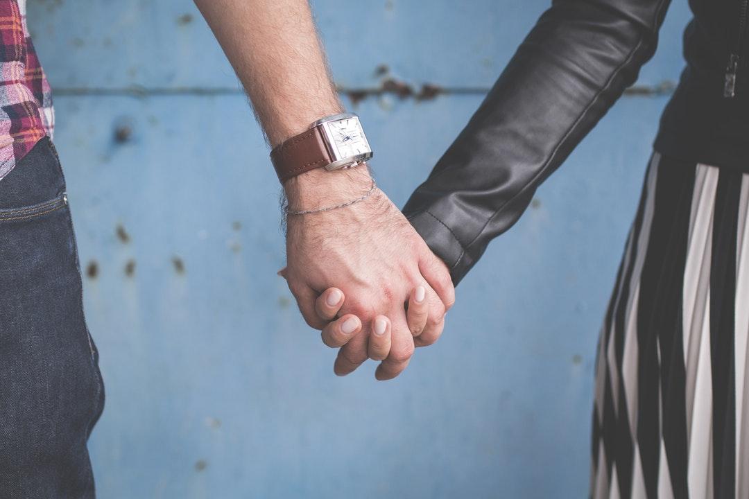 A couple links fingers in front of a blue wall in Olsztyn
