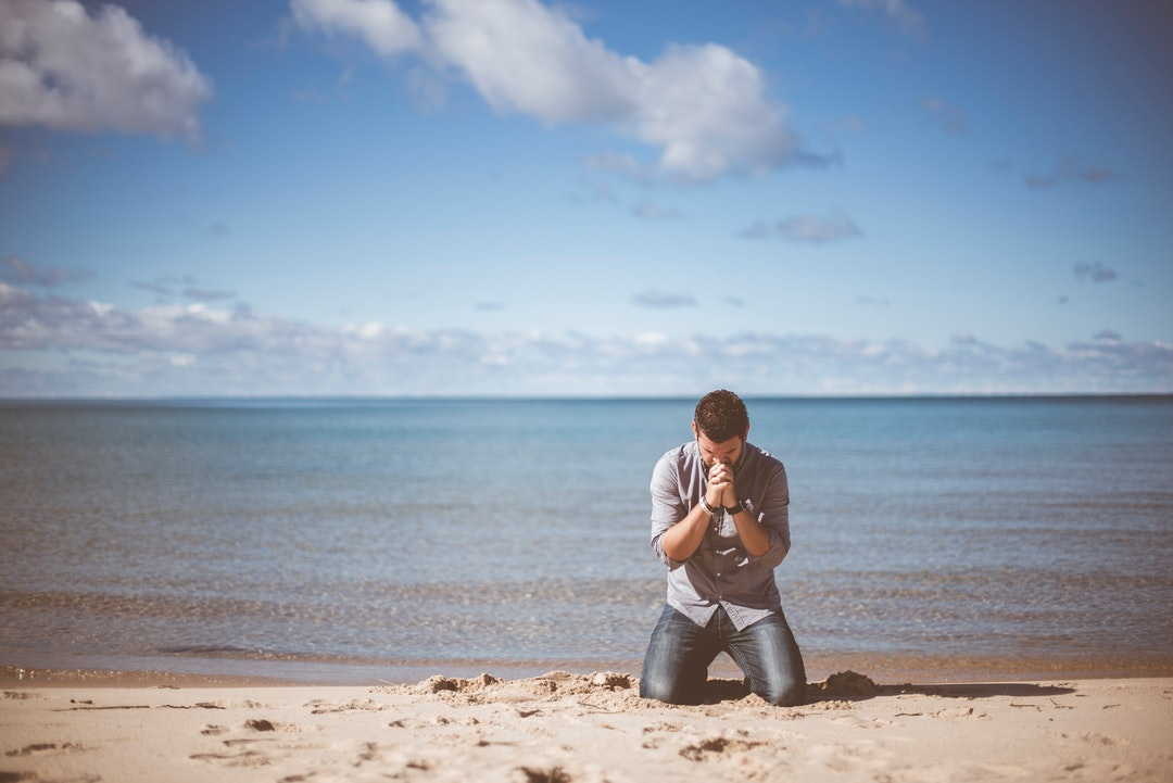 A man in a shirt and jeans kneeling on the edge of a beach with his hands clasped against his chin