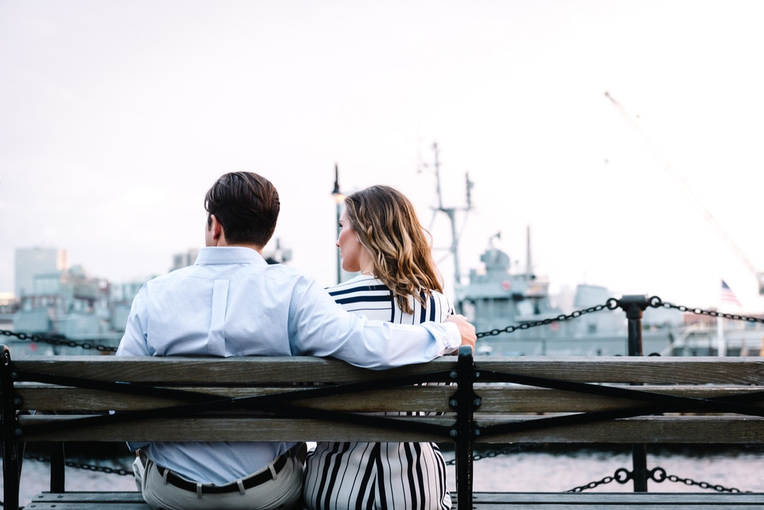 Couple sitting together on a bench by a Boston marina