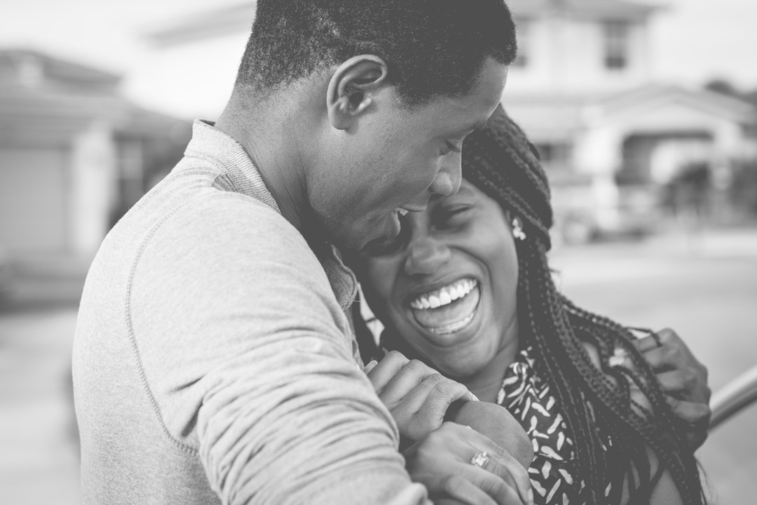 Black and white picture of man and woman holding each other and laughing in Fort Pierce
