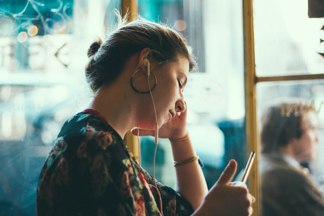 Tired woman rests her pen while working in a cafe and listening to music