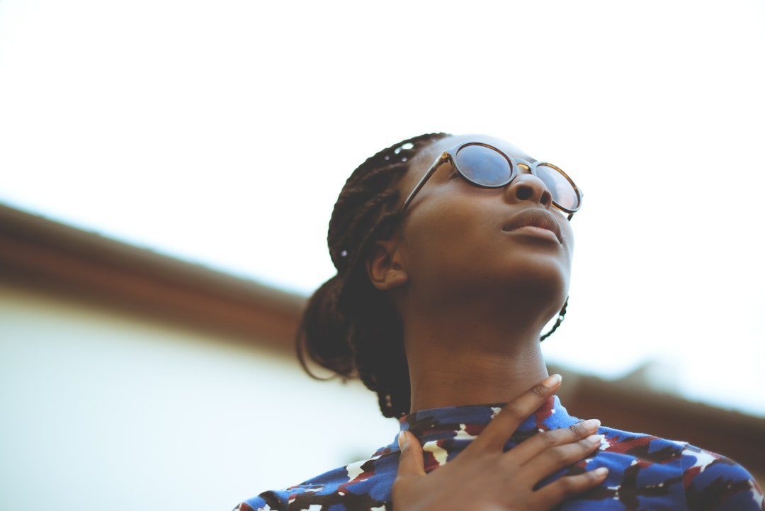 A fashionable young woman in sunglasses and a colorful shirt looking away from a camera.