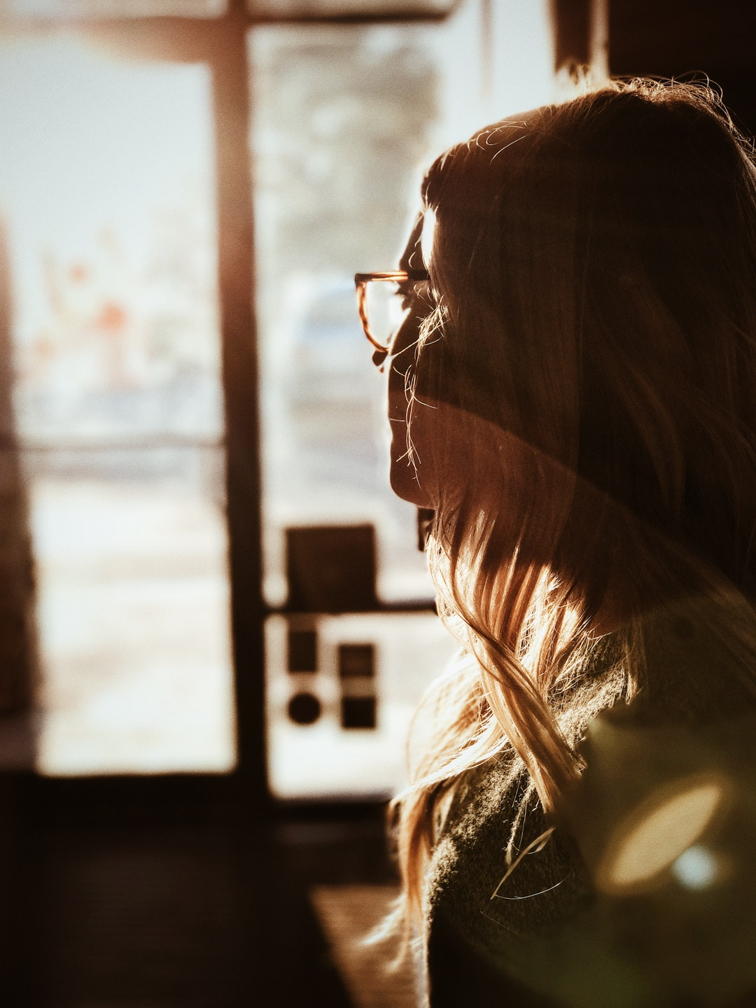 A blonde woman in glasses longingly looking at the window