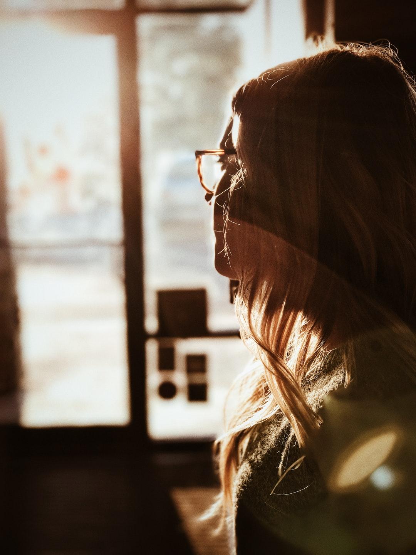 shallow focus photography of woman facing door