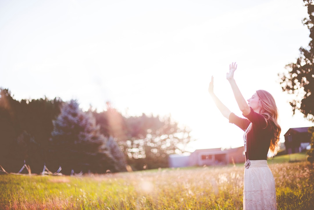 A blonde woman in a field raising her hands to the sky.