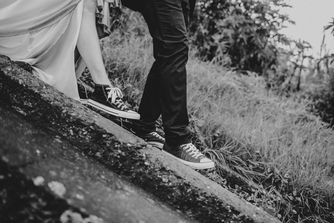 Black and white shot of bride and groom wearing converse shoes walking down stairs near grass