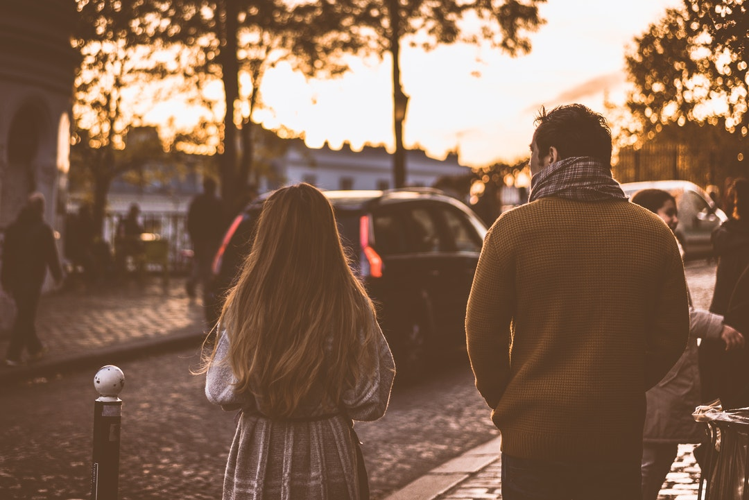A woman and a man walk through a crowd by a cobblestone street