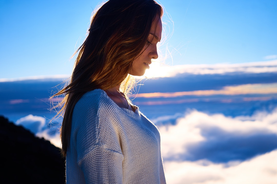 Woman with long hair and sweater at a high altitude looking down during sunset in Route du Volcan