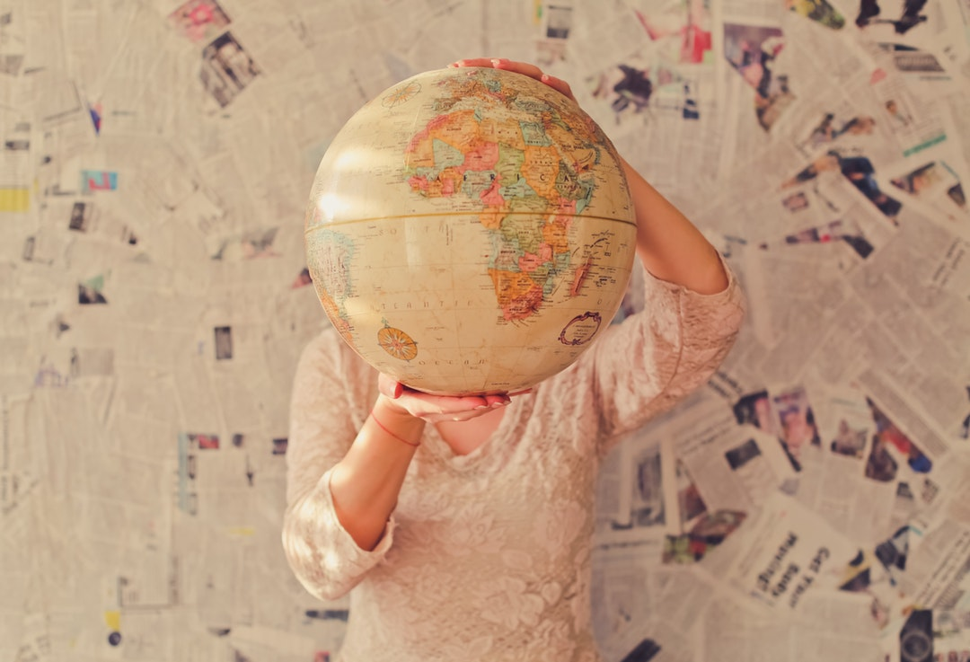 A woman in a lace blouse holding up a globe in front of her head