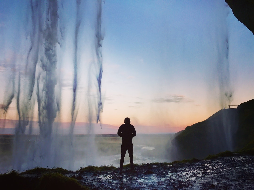 A person staring at the sunset from behind a large waterfall in the Southern Region of Iceland