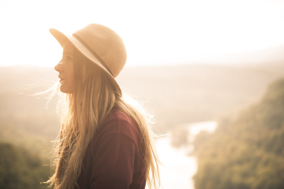 Hopeful woman looking to the side in a hat backlit by the sun