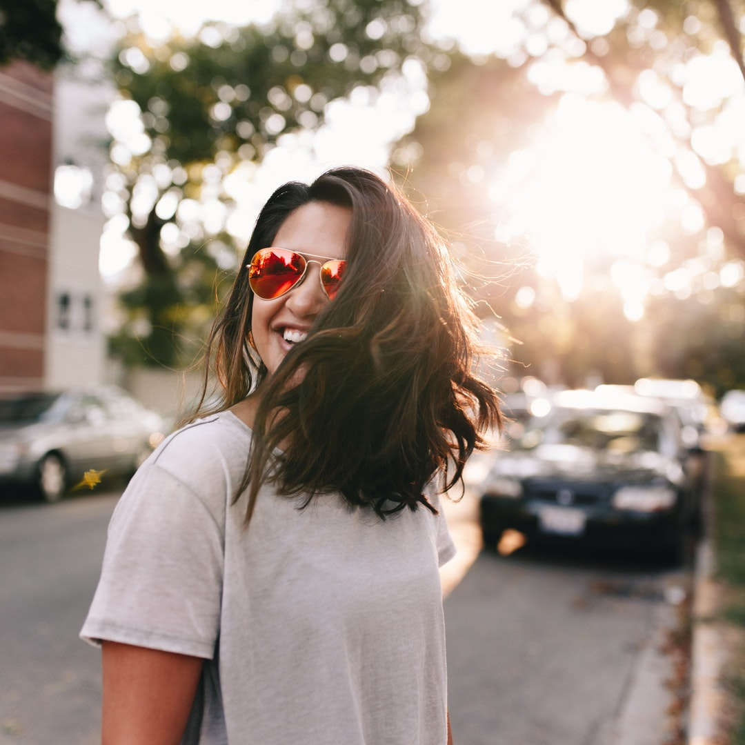 A smiling woman in sunglasses and a t-shirt stands on a sunny street in Chicago