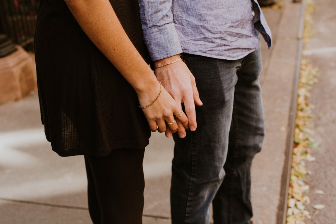 A couple holding hands, standing on a sidewalk. Both are wearing bracelets.