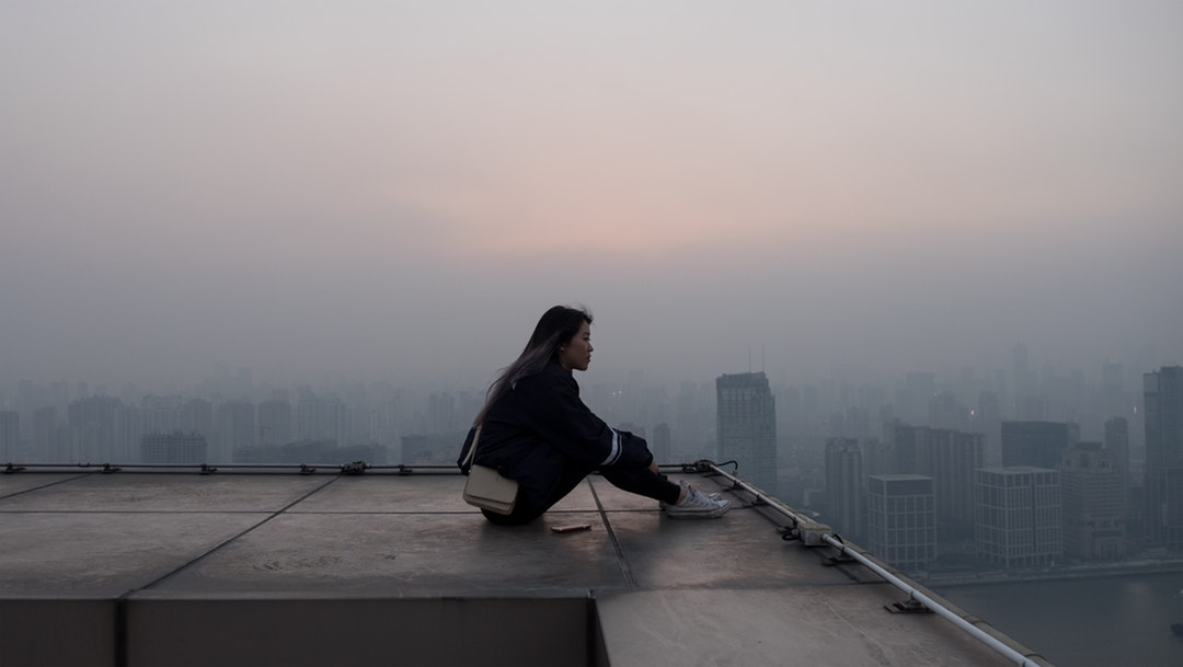 A woman sits looking into the foggy distance atop a building in Shanghai