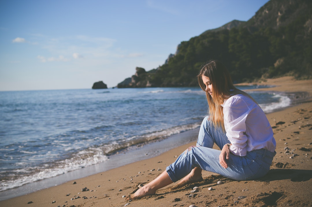 Young woman sitting on a sand beach in white shirt and jeans in Corfu