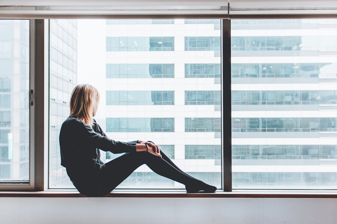 A young blonde woman sitting on a windowsill and looking out the window in Seoul