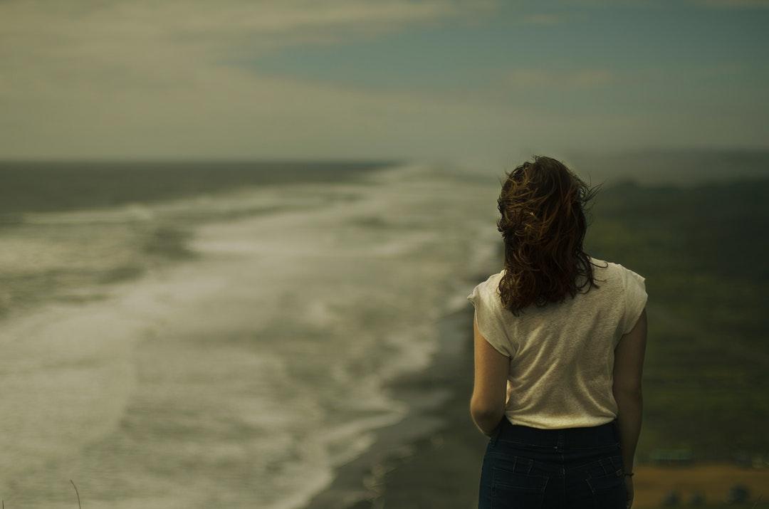 Woman walking away along a wavy ocean shoreline