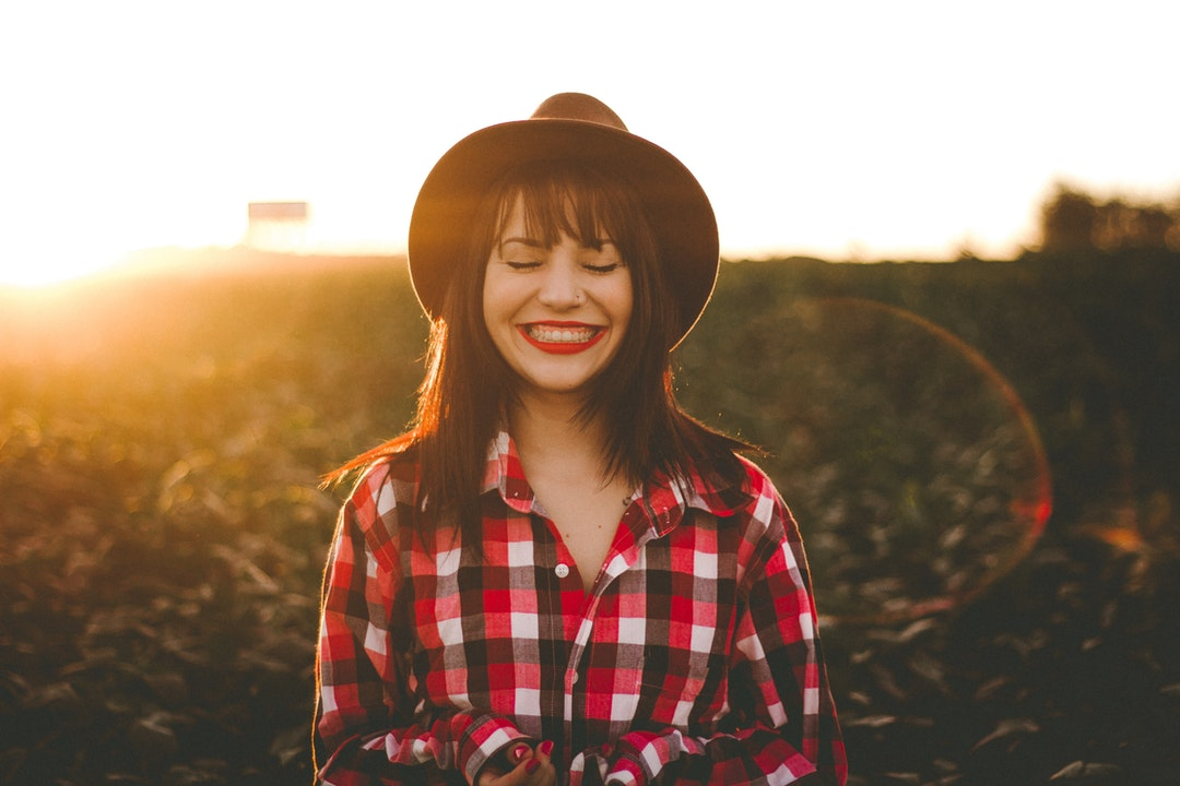 Woman in bright red lipstick, a hat, and a plaid shirt smiling in a sunny field