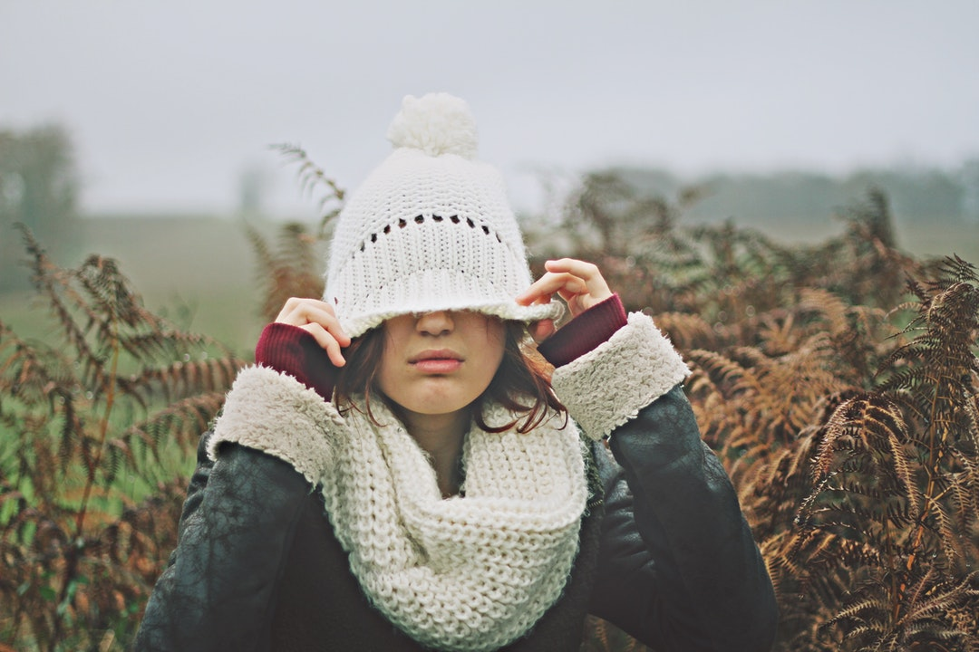 Girl with white scarf covering her eyes with a white knit beanie at Biarritz