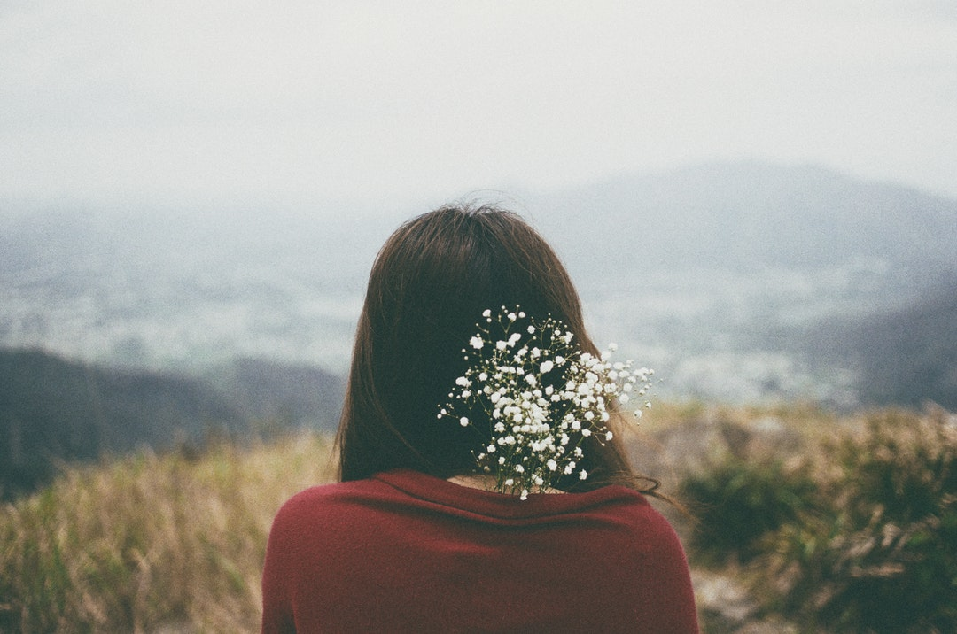 Woman with baby's breath flowers in her hair looking at a field