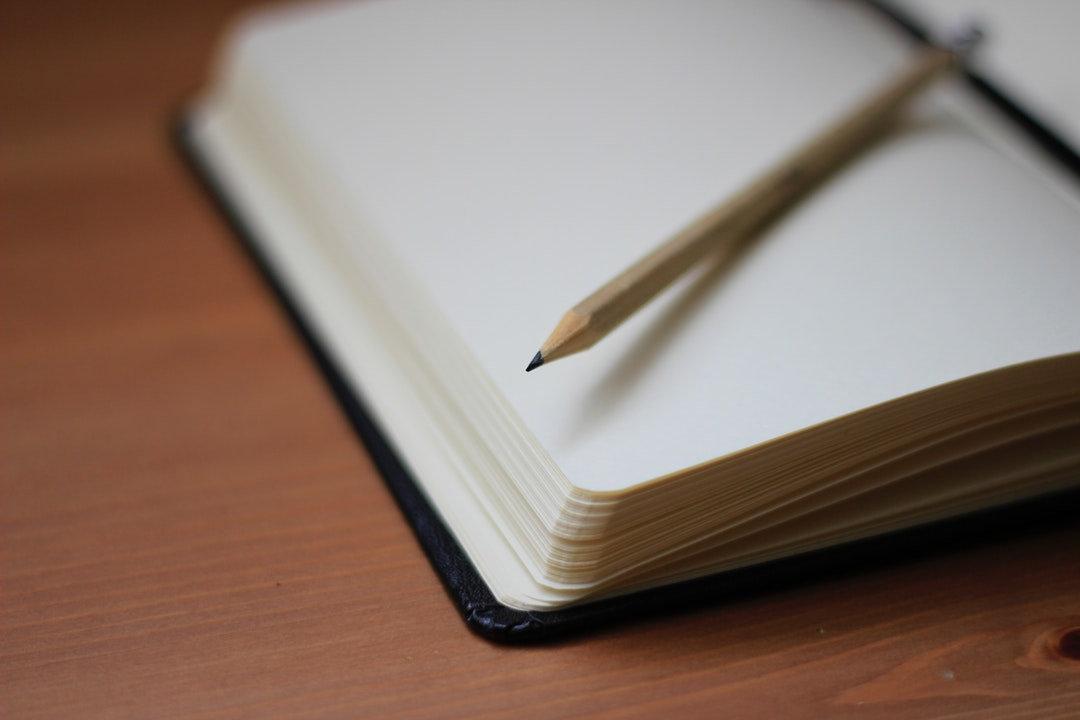 A pencil on top of an open notebook