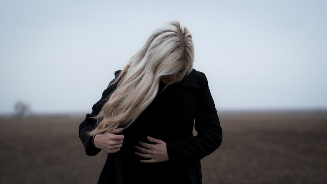 Person with long blonde hair buttoning their coat outside