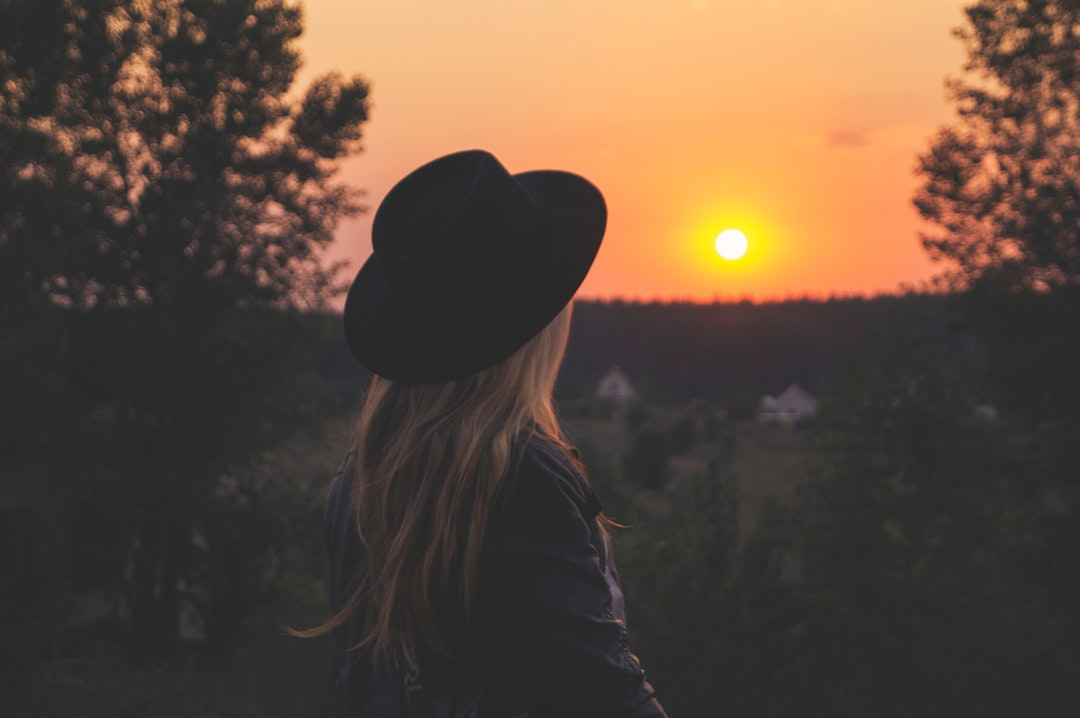 Back view of a blonde woman with a black hat on her head, watching the sunset over trees