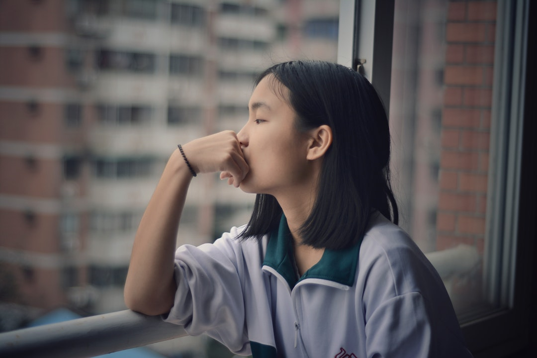 A teenager looks out the window with a hand on mouth and elbows on the railing.