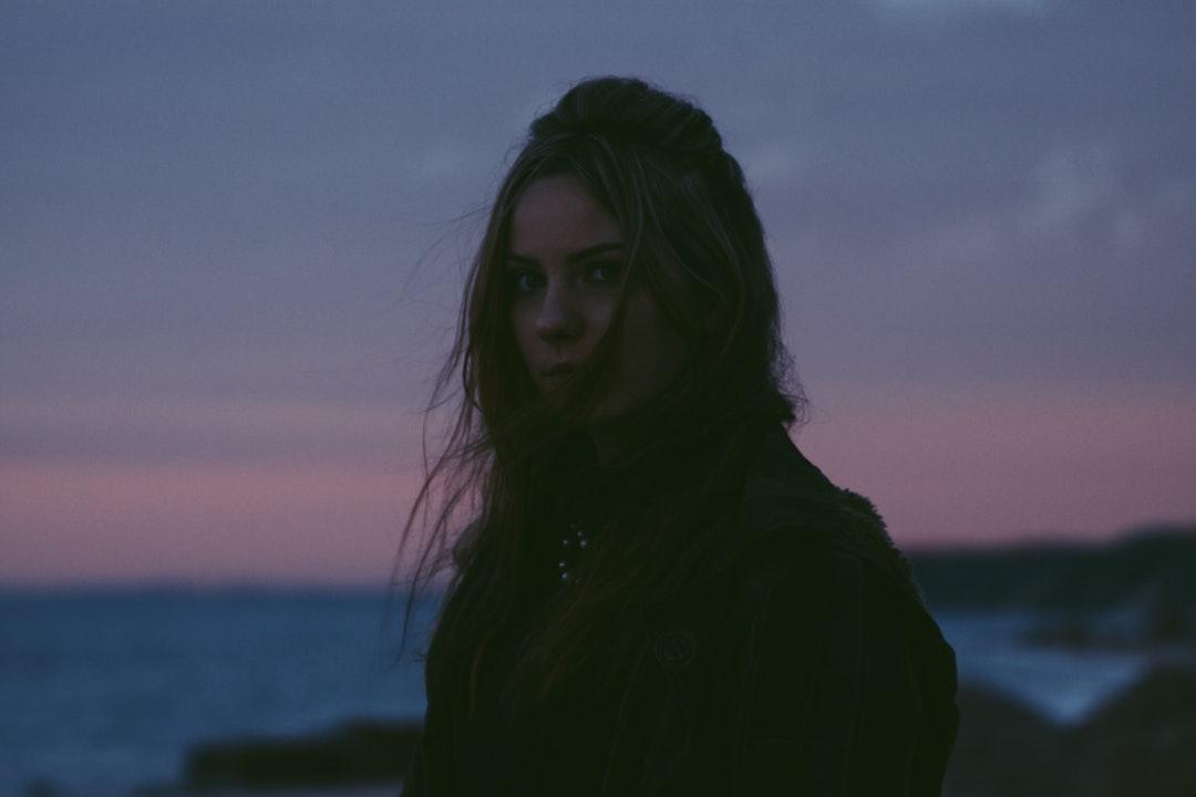 Woman with windblown hair standing near an ocean at dusk