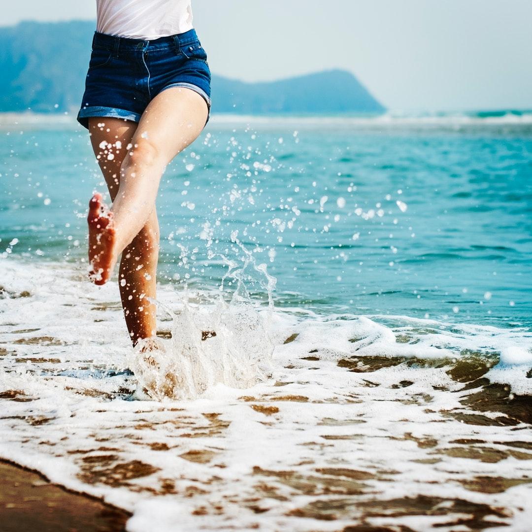 A girl wearing jean shorts splashing her feet in the ocean