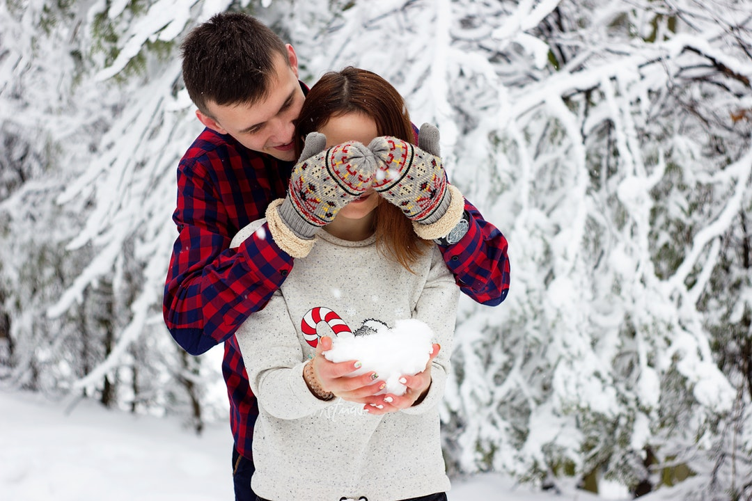 A man stands behind a woman and covers her eyes with his hands in mittens; she is laughing and holding a pile of snow in her hands