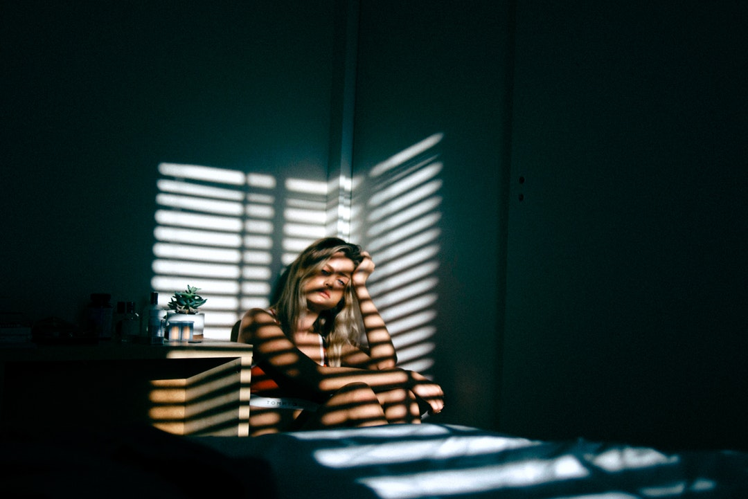 A dejected looking woman sat in a dark bedroom with her hand on her head, with horizontal strips of light shining on her from a blind, Bloomington