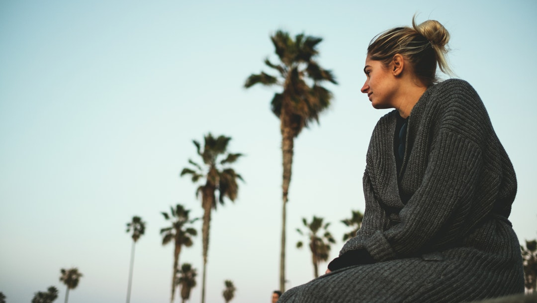 Woman in knitted cardigan sitting by the palm tree boulevard at Ocean Beach Pier