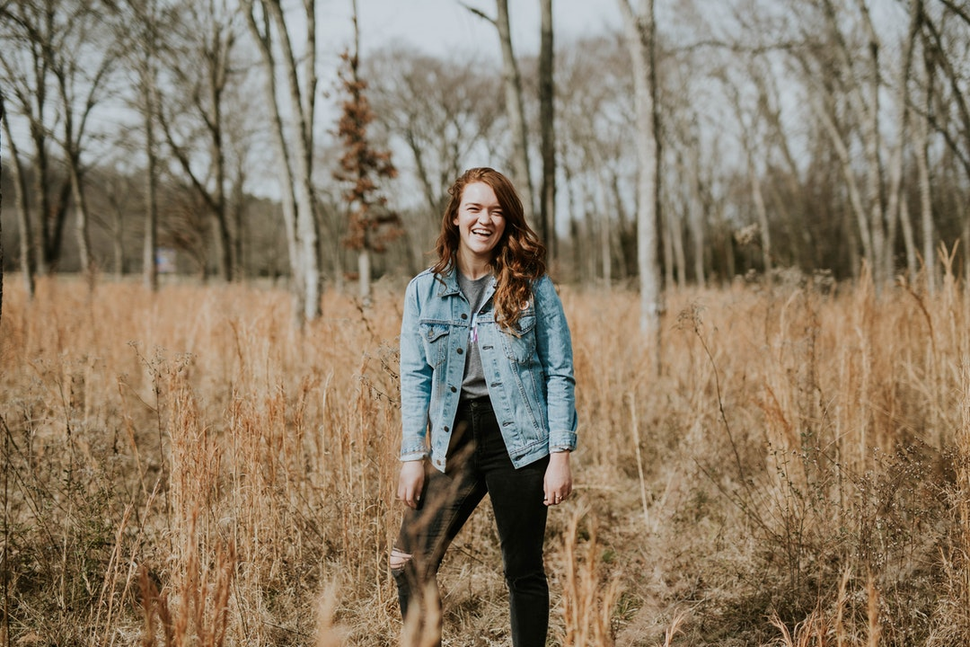 A woman in a denim jacket laughs in a field of long brown grasses and trees