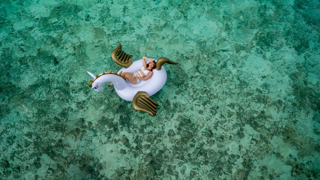 woman wearing white bikini set lying on white and brown unicorn inflatable float