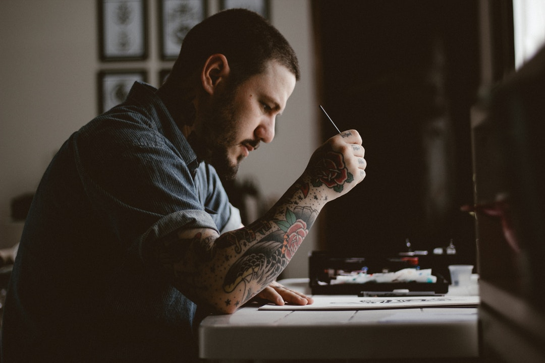 An artist with a tattoo on his arm working at a desk
