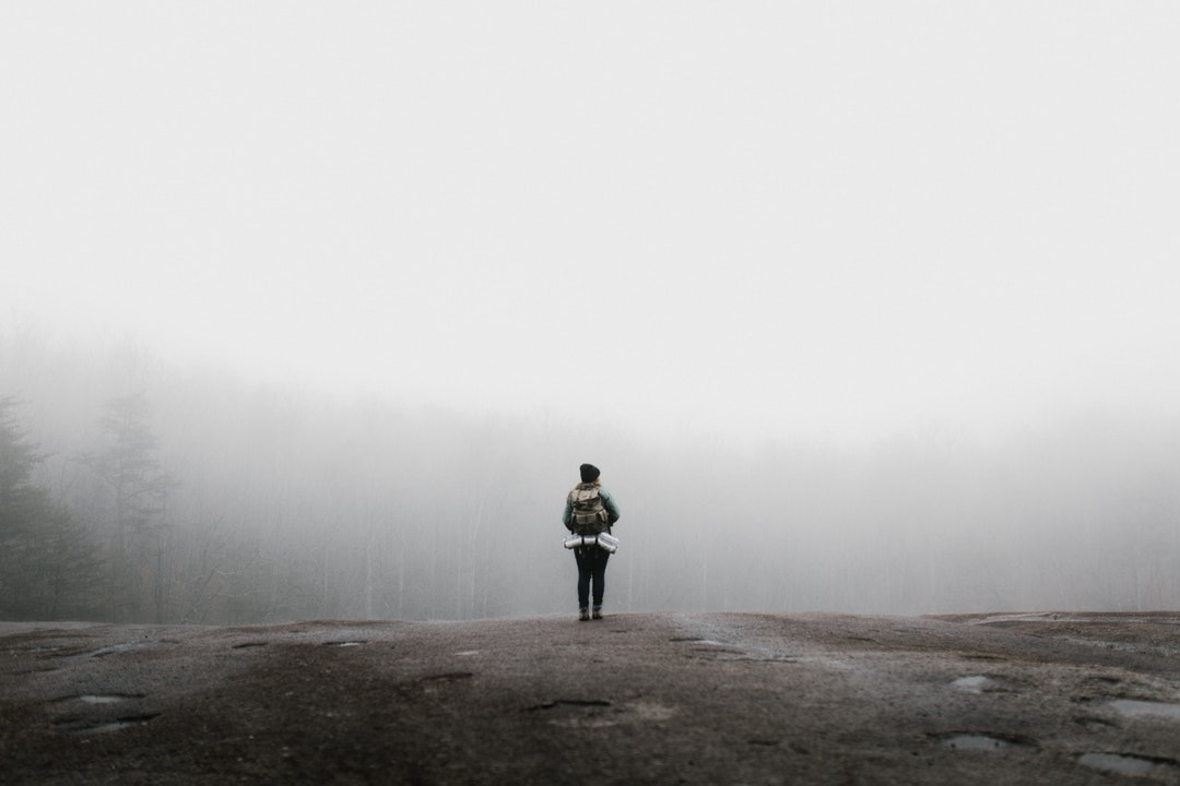 A woman standing on a rock, wearing a backpack with her gear in it, in the fog at Stone Mountain State Park