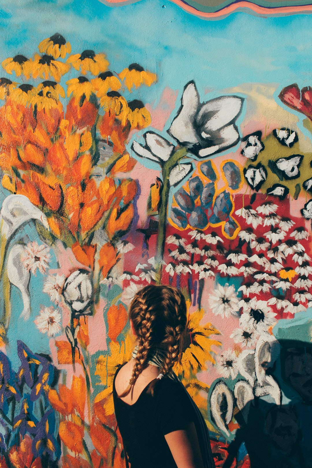 Young woman with plaited hair looking at colorful graffiti artwork in Nashville